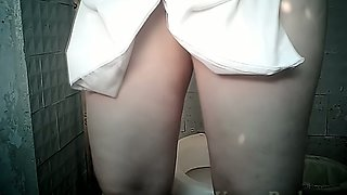 Pale skin stranger woman pulls down her panties and pisses in the toilet