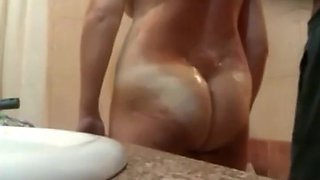 Bent over woman gets oiled up
